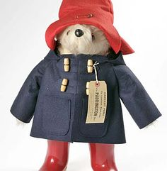 Paddington: A photo of a stuffed blonde teddy bear in a blue duffel coat, red hat and red wellies