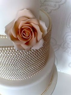 a simply beautiful wedding cake with pearls and a pink rose -- keeping it sweet.