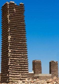 Torens van zonsteen in het Saudische Asir die gebruikt werden als graanschuren. De tegellagen zijn om de torens te beschermen tegen erosie door regen. Foto vanEric Lafforgue.