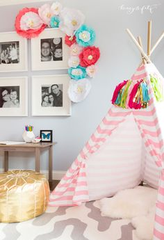 Love the tissue flowers and tissue tassel decor in this adorable teepee area of a girls room!