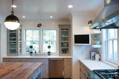 Hicks Pendants hang over a freestanding gray kitchen island fitted with drawers adorned with unlacquered brass recessed hardware topped with butcher block.