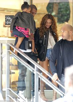 One happy family! The trio were all smiles as they left the store with their burly bodyguard