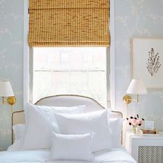 Bed in front of window| bedroom spaces...headboard, bamboo shade, & wall sconces