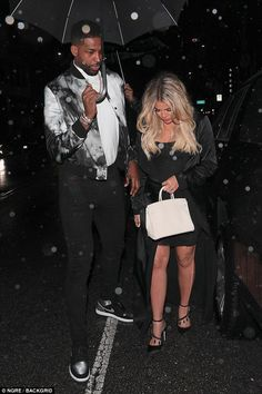 Doting father-to-be: For his part Tristan kept a close eye on Khloe, holding her hand and covering her with an umbrella as they walked inside Beauty & Essex in Hollywood