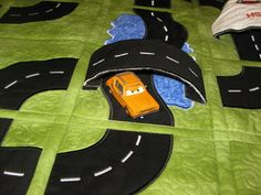 What makes it even cooler is the bridges/overpasses   and the car wash that your cars can drive thru!  These are stitched into the quilt on one side and attached with velcro on the other.   That way when you want to store the quilt, you just release them and they lay flat!