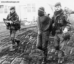 Falklands War, An Argentine Marine Infantry officer is escorted by 40 Commando RM after being captured inside the San Carlos beachhead on 25 May.