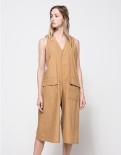 From Toit Volant, a lightweight oversized jumpsuit with boxy silhouette in Camel.  Features wide straps, deep v-neckline, front patch pockets with flaps, button back closure, keyhole back, dropped crotch, cropped length and relaxed fit.  • Lightweight,