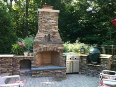 Outdoor fireplace and built in BBQ with a Viking grill and The Big Green Egg, with natural stone veneer. By Signature Outdoor Concepts