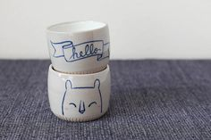 This bear cheerfully greets all who imbibe from the vessel! This ceramic cup was thrown on the wheel, then altered and hand-painted with cobalt.
