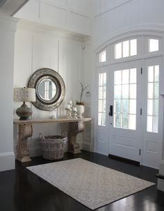 West Beach house- white front door paned glass dark wood floors foyer console table lamp mirror basket arched doorway entryway