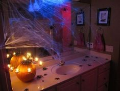 Spider and pumpkin candle holder for bathroom decor.