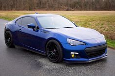 This is a pretty cool looking BRZ. It's probably too low to be practical, but it shows that a dark stealthy look can be pretty cool! Notice that he's blacked out his headlights (taken them apart and painted the chrome bits black), and added yellow foglights. Also, black wheels - OZ Ultraleggeras from the look of things. Also, it's not World Rally Blue - it's the darker blue, which I believe is no longer available on a BRZ.