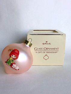 A vintage glass Hallmark keepsake ornament. A Gift Of Friendship. 1984 - with original box  It has a slight pinkish background color with three pictures including a girl and her kitten. Friendship is the happiest gift of all!  The ornament is in good vintage condition with no visible cracks, chips or marks.  Ornament measures approximately a little over 3 x 3  There are nine of these on ebay right now from $7.50 to $12. There are two on Etsy one is $4.88 the other is $14.95. Would say $8.50.