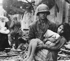 Liberation of Bataan, Feb., 1945. An American soldier carries an injured Filipino girl away from the fighting there. An estimated 100,000 civilians were killed as fighting raged house to house. MacArthur refused to bomb the city with so many civilians present resulting in fierce, close combat.