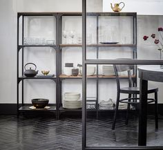 A dining room with two shelving units in black steel with mesh shelves and solid pine shelves. The shelving units are used as storage for glasses, plates, bowls and table napkins.