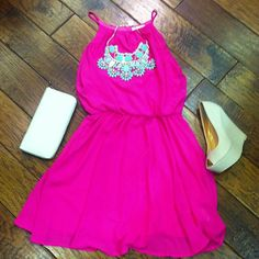 Neon pink dress with teal statement necklace and cream wedges