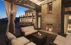 This inviting outdoor space is anchored by a tall stone hearth and can be curtained off for cooler weather enjoyment