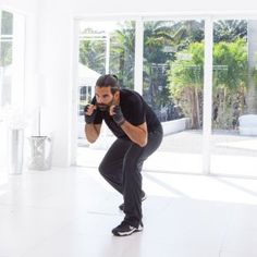 Stand in a sumo stance with feet wider than hip-width apart, toes pointed outward, and hands in a fighting position directly in front of face. Bend knees, push hips backs, and lower body into a squat position while keeping torso upright. Side-crunch one shoulder toward nearest hip. Continuing in a circular motion, round upper back to crunch toward the front of body. Then side-crunch to opposite hip.