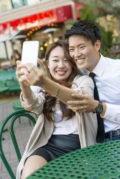 Korean couple taking cell phone photograph at sidewalk cafe