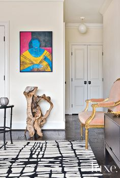 Bright wall art adds a pop of unexpected color to the apartment's foyer.