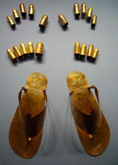 Ancient Egyptian gold sandals, toe and finger stalls Gold Dynasty 18, reign of Thutmose lll ca. 1479-1425 B.C. From the tomb of the three minor wives of Thutmose lll in the Wady Gabbanat el-Qurud, Thebes.  The gold sandals have been decorated to imitate ones crafted of tooled leather that would have been worn by the living. The gold finger and toe stalls were found on the hands and feet of the mummy and are standard elements of a royal burial. Metropolitan Museum of Art, NYC