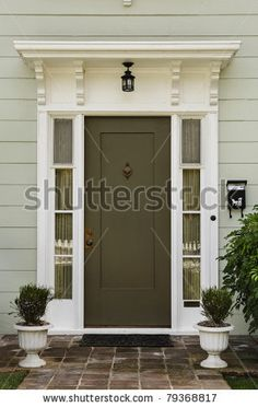 stock photo : The wooden front door of a home with glass panels to each side and a brick porch. The glass is reflecting the homes opposite the door. Vertical shot.