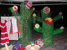 We made this cheerful trio of light and airy cactus made from chicken wire, laced with white Christmas lights and covered with bright green tule. The saguaro cactus, range in height 4' to 9', have Mexican-style tissue paper flowers.These DIY party decorations were for a fiesta fundraiser at Clairemont HS in San Diego. Design and photo by Amy Laurel Hegy @A Tale of Two Tramps