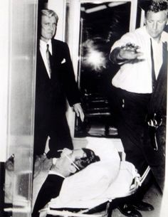 R. kenedy El 4 de junio de 1968 era un día feliz para Robert Kennedy. Se acababa de convertir, por una abrumadora mayoría, en el candidato demócrata a la presidencia. Si nada raro ocurría se convertiría a los 42 años, en el presidente norteamericano más joven de la historia. Para celebrar su triunfo ofició una rueda de prensa en el HOTEL Ambassador de Los Ángeles. Al terminar, un inmigrante palestino llamado Sirhan Sirhan le disparó. Esta foto fue tomada mientras era trasladado al hospital…