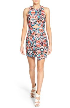 Swooning over this vibrant floral body-con dress with a trendy cutout and asymmetrical hem.