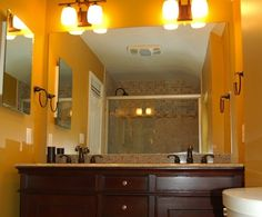 Statement Paint - If your bathroom has lots of Earth-toned accents, you can opt for vibrant paint on the walls. This mustard yellow gives the subtle room a little extra punch.Photo by Ardyiii. Rustic Bathroom Decor, Rustic Decor, Bathroom Colors, Bathroom Grey, Bathroom Ideas, Hallway Colours, Yellow Bathrooms, Round Mirrors, Wainscoting