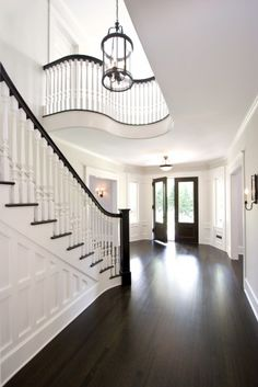 Railing Idea Grand formal foyer with dark hardwood floors and double front doors. Sweeping paneled staircase with white spindles and dark handrail. Curved balcony overlooking stairs, white walls and large glass and iron pendant. House Design, Future House, House, Hardwood Floors Dark, Home, House Goals, Foyer Decorating, Floor Stain Colors, New Homes