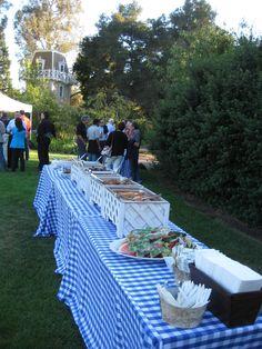 White buffet equipment on blue and white gingham linen.