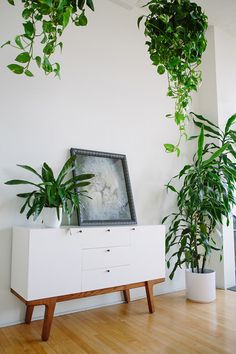 """We love the airy and open vibe in Jon + Nina's Los Angeles loft spotted on Design*Sponge. Their white Scandinavian-style Dumont Buffet blends into the background as their love of plants — both the real thing and botanical prints — takes center stage."""