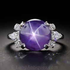 A gorgeous high-domed lavender-blue star sapphire, weighing 11 carats and displaying a distinct, well defined six-pointed star (or asterism), is elegantly presented in platinum between a pair of diamond sprays composed of a pear shape diamond flanked by round brilliant-cut diamonds. An enchanting and colorful classic gemstone ring, by the renowned Philadelphia based jeweler since 1839 - J.E. Caldwell.