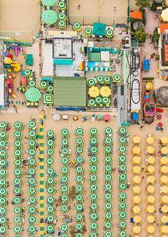 Foto cenital aérea hecha con drone a playa llena de sombrillas en verano.