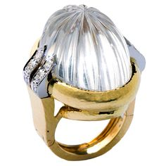 Circa 1970s -- Large fluted dome rock crystal set in 18 karat gold ring with diamond accents by David Webb.