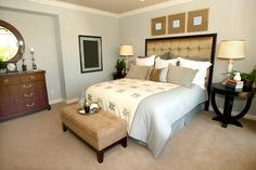 Stylish contemporary master bedroom with carpet, wood furniture and padded head-board
