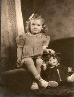 Vintage photo of a little girl with her doll, circa 1930's.