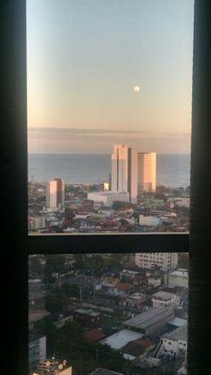 O dia cinza e a lua lá em cima, cheia e silenciosa.