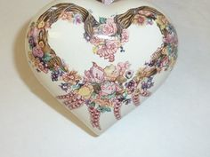 This lovely vintage pomander features a heart shape with a wreath and flower design in shades of pink.  It comes with a sachet of organic lavender in a matching pink organza drawstring bag.  Also included is a floral gift box (new).  In excellent vintage condition. No chips or cracks.  Measures 3 1/4 x 3.  Q1340860