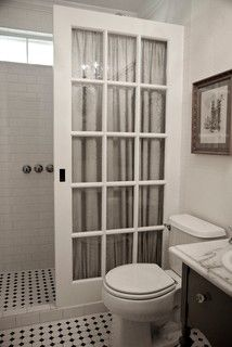 """""""A glass shower wall exceeded the entire cost of the remodel,"""" says Bradley Ross. Instead of shelling out for the expensive glass, he found an old French pocket door, painted & sealed it multiple times & added tempered shatterproof glass. """"To finish the look and protect the glass from water spots, we placed a poly brocade curtain behind the door,"""" he says. The total costs were just a fraction of the cost of a glass enclosure, and now the shower has a unique architectural element."""