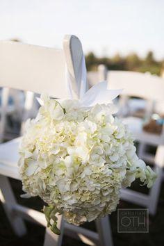 White flower arrangement pew / chair decoration.