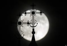 """The """"supermoon"""" appears behind a steeple with crosses of an Orthodox church in the town of Novogrudok, 150 km (93 miles) west of Minsk, Belarus, late Saturday, May 5, 2012. The moon was the closest it will get to the Earth this year _ and appeared 14 percent larger because of that. At its peak it was about 221,802 miles from Earth. (AP Photo/Sergei Grits)"""