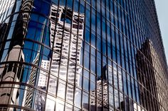 Adjacent skyscrapers are reflected in the glass facade of 1111 Travis Street in Downtown Houston.  See more #photos at 75central.com