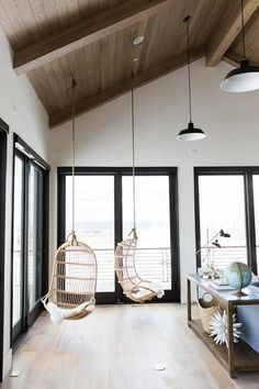 In a charming country living room illuminated by two black vintage bar pendants and recessed lighting, a gorgeous vaulted plank ceiling holds a pair of Two's Company hanging rattan chairs hanging over wood floors accented by black framed sliding patio doors framed by white walls painted in Simply White by Benjamin Moore.