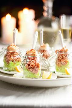 Verdeel de sla over 4 glazen of vierkante mini-accubakjes. Schep de garnalen erop en giet de cocktailsaus erover. Garneer met partjes citroen.