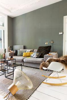 Salon avec des mur peints en kaki et avec une chaise à bascule Eames