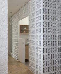No corredor onde está a entrada da cozinha e do banheiro, a parede foi substituída por blocos de cobogós (Foto: Djan Chu/Divulgação)