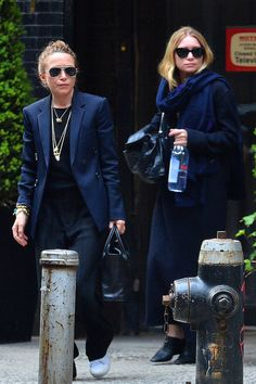Mary-Kate and Ashley Olsen step out in NYC wearing layered black and navy looks. Mary-Kate's masculine-inspired look consisted of layered necklaces, a blazer, simple tee, croc bag, wide leg pants and white sneakers. Ashley wore an oversized scarf, sweater maxi dress, and heeled mules.