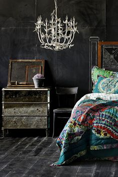 chandelier. chalkboard walls. dark floors. colorful comforter. mirrored dresser.
